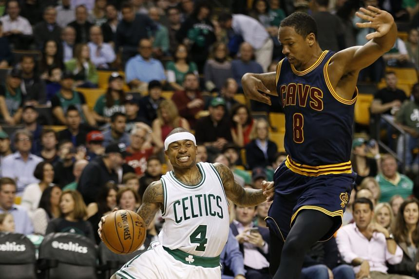 Celtics point guard Isaiah Thomas is tripped by Cavaliers forward Channing Frye during the game at TD Garden. He overcame a recent shooting slump to top score with 31 points in Boston's 103-99 victory over the holders.