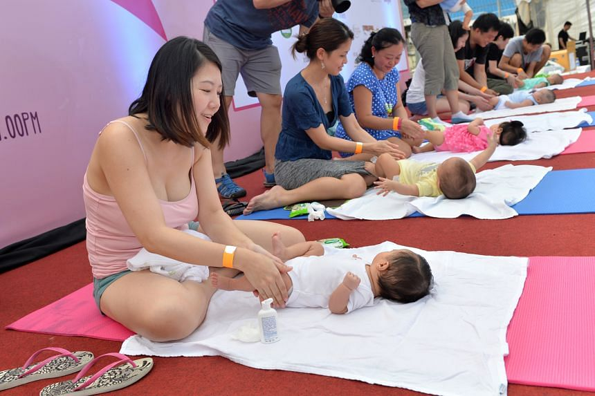 Mothers learning how to massage their babies at the inaugural Great Eastern SuperMom Carnival in 2015. While the public service's pilot scheme to offer more unpaid infant-care leave has been lauded for giving parents more time to spend with their bab