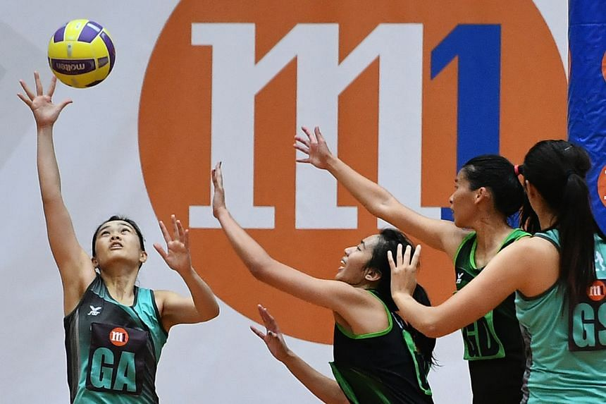 Tiger Sharks' Zhang Ailin (left) reaching for the ball during the Netball Super League opening match at Toa Payoh Sports Hall yesterday. The Sharks, who have six national players, beat the Magic Marlins 54-48.