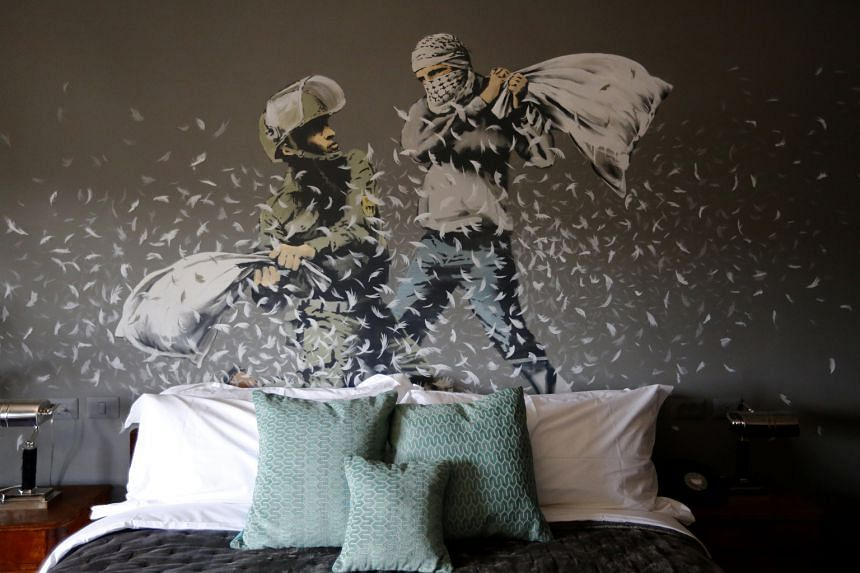 Above a bed in The Walled Off Hotel, an Israeli soldier and a Palestinian protester fight with pillows.