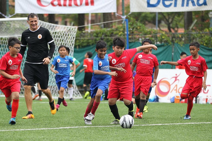 Children aged six to 12 years old playing football at Jurong East Stadium as ActiveSG Football Academy principal Aleksandar Duric, a former Lion, looks on. The academy will merge its junior programme with the FAS' Cubs Programme.