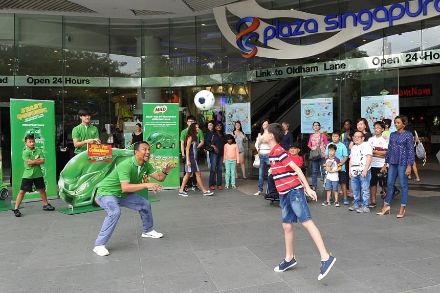 Singapore football legend Fandi Ahmad with one of the fans yesterday at Plaza Singapura as part of a promotional campaign with Milo. Fandi was joined by his daughter Iman and son Iryan.