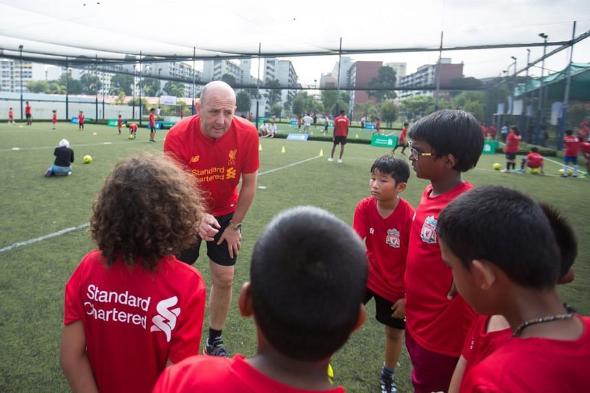 Former Liverpool star Gary McAllister shares some tricks of the trade with a group of young players at the Standard Chartered Trophy 2017 Singapore Qualifying Tournament.