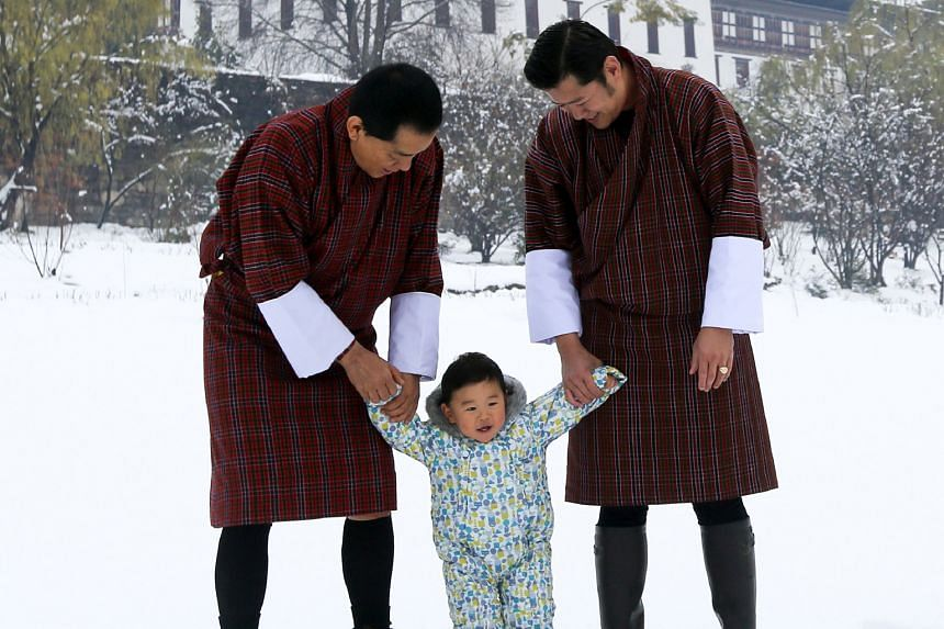 The King of Bhutan Jigme Khesar Namgyel Wangchuck (right) and his father, the fourth King of Bhutan Jigme Singye Wangchuck, supporting Bhutan's young prince Gyalsey Jigme Namgyel in Thimphu on March 11. Prince Jigme, who celebrated his first birthday