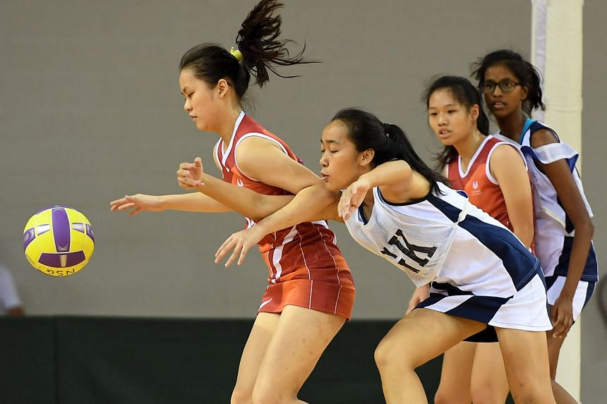 Above: CHIJ goalkeeper (in white) Tina Leong defends against SSP's goal shooter Priscilla Wong. CHIJ won the B Division final 42-18. Left: Dunman's squad celebrate winning their school's first C Div netball title in 10 years.