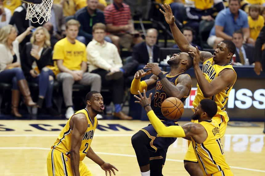Cleveland Cavaliers forward LeBron James (23) gets fouled while going up for a shot against the Indiana Pacers' Paul George (13) and Kevin Seraphin during the reigning champions' opening-round Eastern Conference play-off series. James now has a total