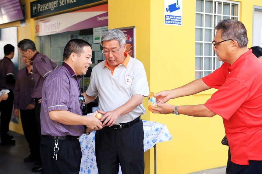 Above: SBS Transit chief executive Gan Juay Kiat handing out packed food to bus driver Yu Yong Ming.