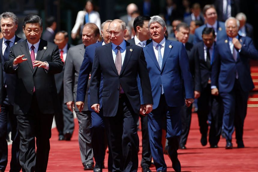 Chinese President Xi Jinping proceeding to take a group photo with his Russian counterpart Vladimir Putin and other leaders during the forum at Yanqi Lake, north of Beijing, yesterday. Mr Putin is among leaders who have given the thumbs-up to the Bel