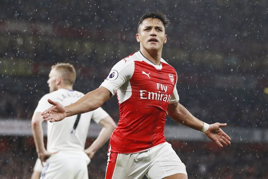 Alexis Sanchez celebrates scoring Arsenal's second goal in driving rain to complete a 2-0 win over Premier League bottom side Sunderland. The Gunners may miss out on the Champions League even if they beat Everton.