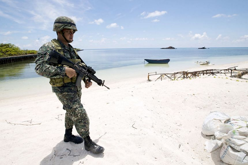 A Filipino soldier patrolling Pagasa island in the South China Sea. China has overlapping claims to territories in the waterway with Asean member states Brunei, Malaysia, the Philippines and Vietnam, as well as Taiwan.
