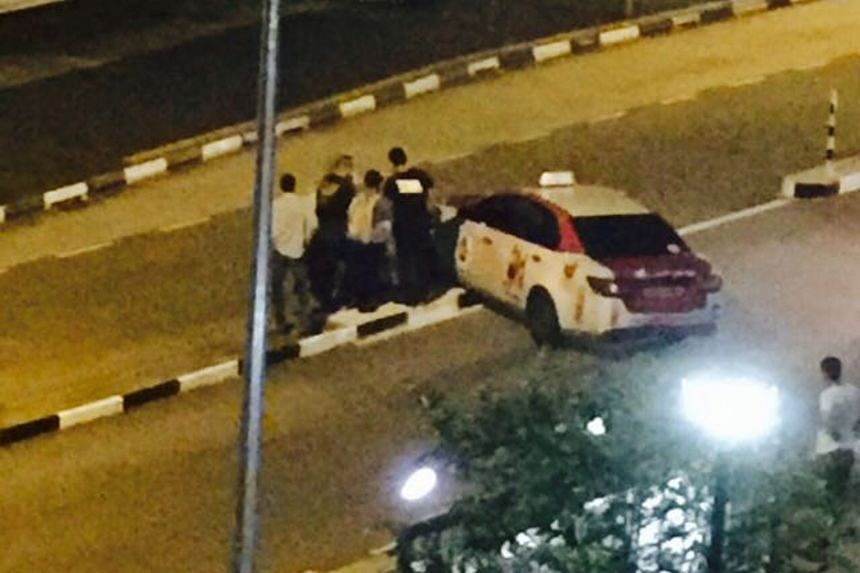 Passers-by helping to move a cab that was stuck on a road divider in Choa Chu Kang Avenue 5 last Friday night. The taxi was successfully moved only after about 10 people gathered to help.