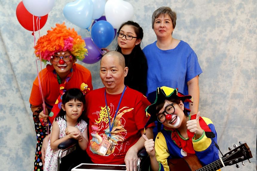 Mr Esmond Goh, with his wife Joanne Lio and daughters Lucia, six, and Lois, 12, having their family photo taken with HCA Hospice Care volunteers, who doubled up as make-up artists, clowns and chaperones.