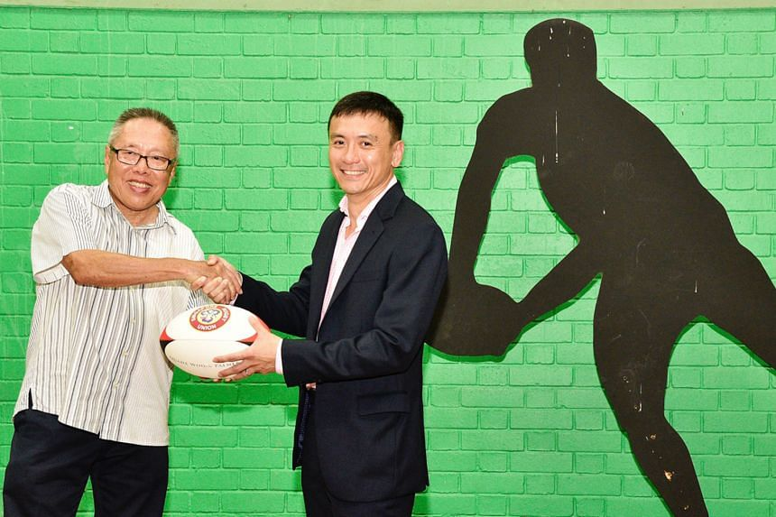 Low Teo Ping, (left) the outgoing president of the Singapore Rugby Union, shaking hands with his successor Terence Khoo, whose aim is to attract more people to the sport.