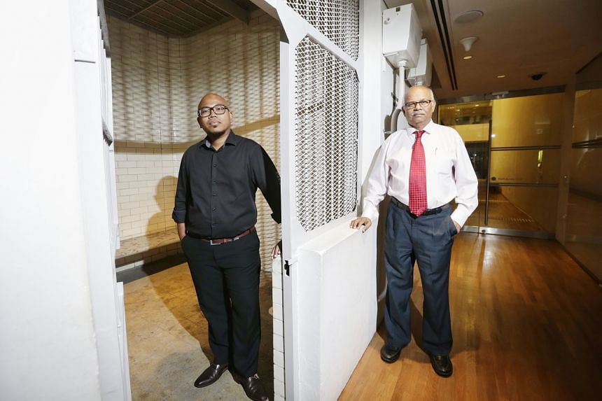 Supreme Court staff Muhd Hakim, 39, (far left) and S. Kathiarasan, 69, at one of the two holding cells that have been preserved. The other cells and passageways have been turned into office space for National Gallery staff.