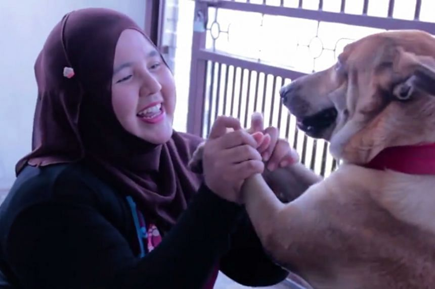 "Ms Nurhanizah Abdul Rahman with Bubu in a video entered in a competition. Jakim said intentionally touching dogs was ""highly disturbing"" and went against Islamic teachings."