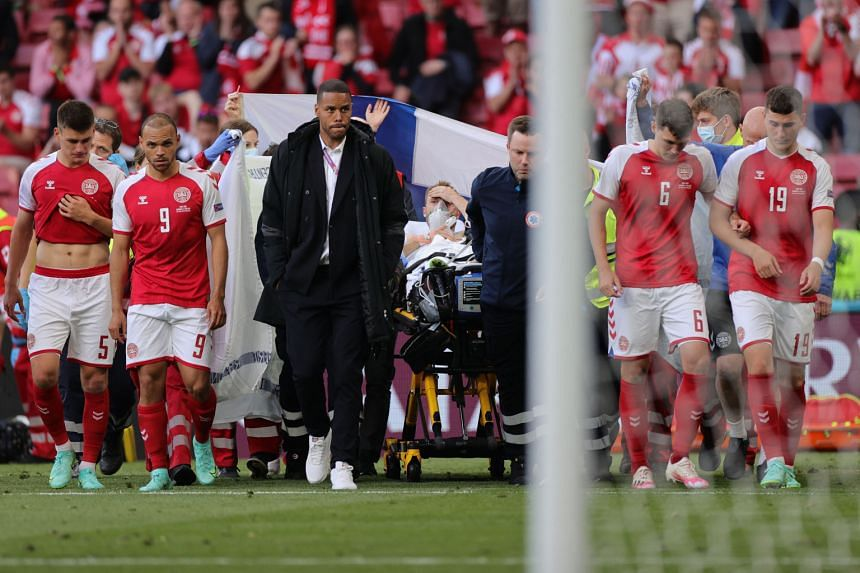 Denmark's players escort Denmark's midfielder Christian Eriksen (centre) as he is evacuated after collapsing on the pitch.