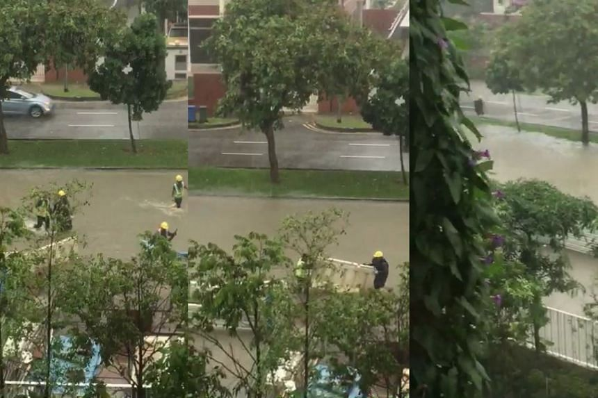 Workers wade through shin-deep water after heavy rain causes flash floods in Tampines.