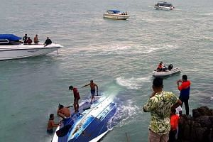 Tourists being rescued by Thai marine police officers and rescuers after a speedboat capsized at sea off the coast of Koh Samui resort island, on May 26, 2016.
