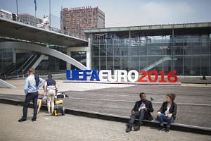 Pedestrians sit near an Uefa Euro 2016 sign in Lille, France, on June 5, 2016.