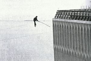 DOTTING THE SKY : Philippe Petit can be seen as a small speck between the Twin Towers (above) as a jet flies over during his high-wire walk in 1974. He warms up with a handstand (right) as the New York skyline looms below him.