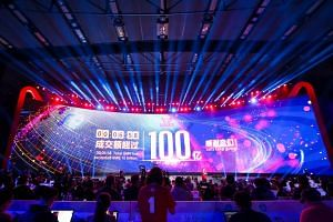 A large screen shows total gross merchandise volume, a measure of sales, exceeding 10 billion yuan after six minutes and 58 seconds during the 2016 Tmall 11:11 Global Shopping Festival gala.