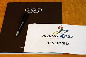 "A sign is placed on a table for members of the Beijing 2022 delegation at the start of the Executive Board meeting at the International Olympic Committee (IOC) headquarters in Lausanne on July 7, 2014. Beijing promised a ""frugal"" Winter Olympics"