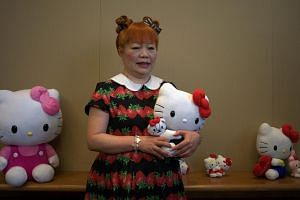 Yuko Yamaguchi, the third designer of Japanese cartoon and global mega-brand Hello Kitty, poses with various dolls during a press conference in Hong Kong on July 17, 2014.The flamboyant designer of Japanese cartoon and global mega-brand Hello&n