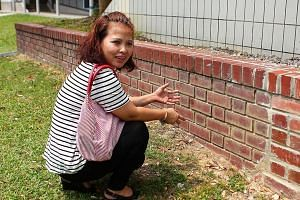 She then got Mr Tan to change into the clean shorts and asked him to sit on a nearby brick ledge, while she knelt before him and started to wipe the faeces off him. -- PHOTO:  THE NEW PAPER