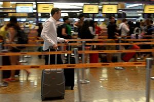 Travellers at a check-in counter at Changi Airport's Terminal 2 on Oct 29, 2014. -- PHOTO: ST FILE