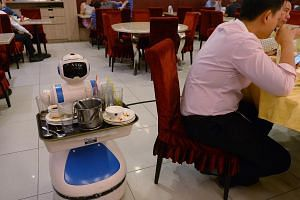 A flying robotic waiter served visitors at the National Productivity Month exhibition in Singapore last month while a robot (above) clears dishes at Supreme Tastes Jiang Nan Chun in Marina Square. -- PHOTO: NG SOR LUAN