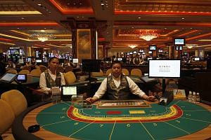 Croupiers at gaming tables inside a casino at Sands Cotai Central in Macau in this 2012 file photo. Gambling revenue inf Macau, the world's biggest gambling hub, fell 2.6 per cent last year. -- PHOTO: REUTERS