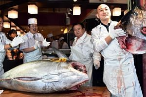 Mr Kiyoshi Kimura (second from right), president of the firm behind Sushi-Zanmai restaurant chain, cut the 180.4kg bluefin tuna at his main restaurant near Tokyo's Tsukiji fish market yesterday. Increasing pressure has been put on Japan to reduce con