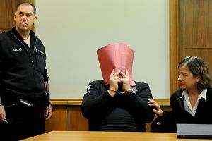A picture taken on Dec 19, 2014 shows former nurse Niels H (center), charged with multiple murder and attempted murder of patients, in hand-cuffs covering his face with a folder next to a clerk (left) and his lawyer Ulrike Baumann in the dock of the