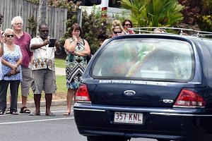 Local residents line the road as a hearse carrying one of the coffins of the eight children in Cairns, Australia, on Jan 10, 2015. --  PHOTO: EPA