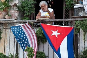 A Cuban gives the thumbs up from his balcony decorated with the US and Cuban flags in Havana, on Jan 16, 2015. -- PHOTO: AFP