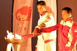 Former national footballer Fandi Ahmad (right) lighting the SEA Games cauldron with his eldest son Irfan Fandi. -- ST PHOTO: SEAH KWANG PENG