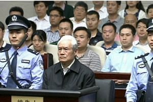 Zhou Yongkang, China's former domestic security chief, sits between his police escorts as he listens to his sentence in a court in Tianjin, China, in this still image taken from video provided by China Central Television and shot on June 11, 2015. --