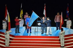 Tunku Imran, president of the Olympic Council of Malaysia, receiving the SEA Games Federation flag from Singapore National Olympic Council president Tan Chuan-Jin last night.