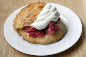 A dollop of cream completes the strawberry shortcake dessert.