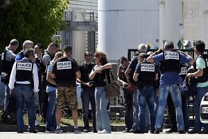 French police secure the entrance of a gas factory in eastern France. An attacker carrying an Islamist flag killed one person and injured several others, according to a legal source.