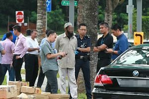 Police officers with the Singaporean man who drove the 7-series BMW sedan.