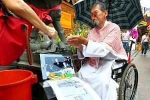 'Parrot Man' Zeng Guoyan selling tissue paper outside a temple at Waterloo Street.
