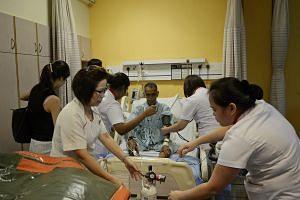 Nurses preparing Mr Atan Bin Bidin for the move to Ng Teng Fong General Hospital.