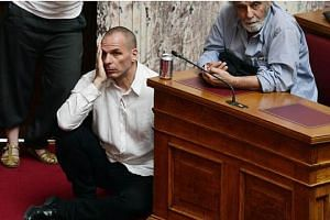 The picture that says it all? Greece's Finance Minister Yanis Varoufakis sitting on the floor with his head in his hands as he listens to Prime Minister Alexis Tsipras addressing Parliament in Athens.