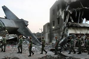 Search and rescue personnel walk at the crash site of an Indonesian Air force C-130 Hercules aircraft in Medan, northern Sumatra province, on July 1, 2015.