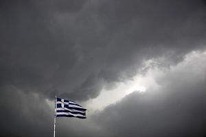 A Greek national flag fluttering atop a building in Athens.