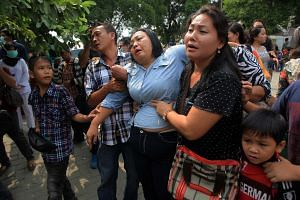 Relatives of the victims of a crashed military airplane mourn outside a hospital in Medan, North Sumatra, Indonesia on July 1, 2015.