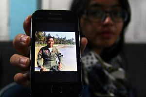 A relative holds up a photograph of Indonesian Air Force captain Sandy Permana, who was on board the C-130 Hercules aircraft that crashed in Medan, northern Sumatra on June 30, 2015.