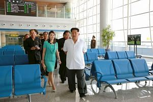North Korean leader Kim Jong Un (in white) and his wife Ri Sol Ju (in green) inspecting the new terminal building of Pyongyang International Airport in this undated photo released by North Korea's Korean Central News Agency (KCNA) on June 25, 2015.