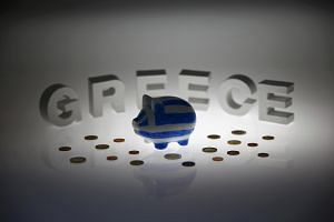 A piggybank painted in the colours of the Greek flag stands amongst various euro coins in front of letters spelling the word 'GREECE' in this picture illustration taken in Berlin, Germany on June 30, 2015.